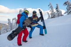Smiling snowboarders enjoying adventure in wilderness Stock Image