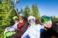 Smiling snowboarders in ski masks on elevator Royalty Free Stock Photo