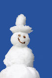 Smiling snowman and blue sky. Smiling snowman against blue sky royalty free stock image