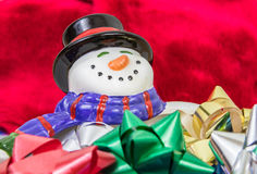 Smiling Snowman with Bows. A horizontal closeup photo of a smiling snowman bowl with multicolored bows in it and a red velvet background Royalty Free Stock Images
