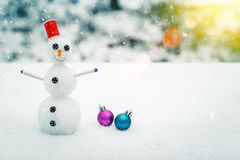 Smiling snowman and Christmas decorations in the forest during a snowfall. Picturesque winter landscape. Stock Photos