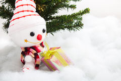 Smiling snowman with gift box and christmas tree Stock Photos