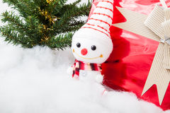 Smiling snowman with gift box and christmas tree Stock Image