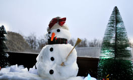 Smiling snowman near the cold windows. With various decorations with christmas three Royalty Free Stock Photo