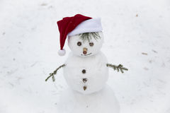 A smiling snowman in red hat of Santa Claus Stock Photo