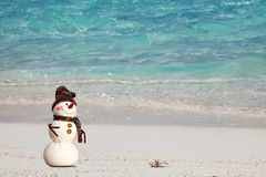 Smiling snowman with and small crab relaxing on tropical beach. New Years and Christmas holidays in hot countries concept Royalty Free Stock Photo