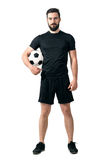Smiling soccer or futsal player wearing black sportswear holding ball under his arm looking at camera. Full body length portrait isolated over white background Stock Photos