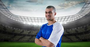 Smiling soccer player with arms crossed at stadium Royalty Free Stock Images