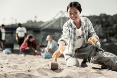 Smiling socially active woman wearing gloves gather empty coffee cups on beach. Gathering cups. Smiling socially active women wearing bright yellow gloves gather stock photo
