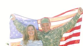 Smiling soldier with big USA background behind the back outdoor. Portrait of cheerful military man with his family in the park stock video
