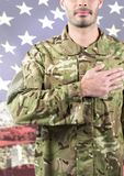 Smiling soldier putting his hand on his heart against american flag background. Digital composite of Smiling soldier putting his hand on his heart against Stock Photos