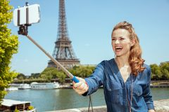 Smiling solo tourist woman taking selfie using selfie stick stock photo
