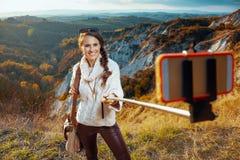 Smiling solo traveller woman taking selfie using selfie stick stock photos