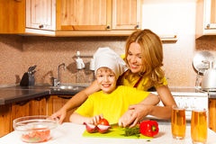 Smiling son cuts vegetables on table with mother Royalty Free Stock Photography