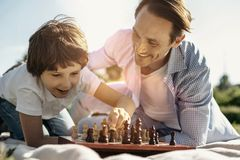 Smiling son and dad playing chess. Favourite game. Joyful laughing kneeling boy playing chess with his dad enjoying the nature and his dad smiling Stock Images