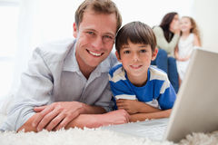 Smiling son and dad using laptop on the carpet Stock Photography