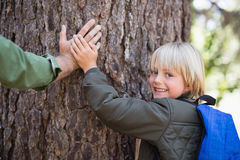 Smiling son with father father touching tree trunk in forest. Portrait of smiling son with father father touching tree trunk in forest Stock Photos