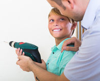 Smiling son helping proud father to drill Royalty Free Stock Images