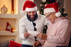 Smiling son and his father watching photo and share memory on Ch. Smiling son and his elderly father watching photo and share memory on Christmas eve stock photography