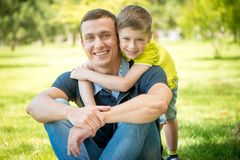 Smiling son hugging his father in the park Royalty Free Stock Photos