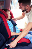 Smiling son in infant car seat being put in back of car by carin Stock Photos