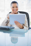 Smiling sophisticated businesswoman holding tablet computer. Smiling sophisticated businesswoman in bright office holding tablet computer royalty free stock photography