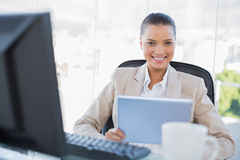 Smiling sophisticated businesswoman holding tablet pc. Smiling sophisticated businesswoman in bright office holding tablet pc Stock Images