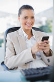 Smiling sophisticated businesswoman text messaging. In bright office royalty free stock photography