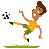 Smiling south american cartoon football player kicking the ball in mid-air. Smiling south american cartoon footballer wearing yellow shirt and green shorts Stock Images