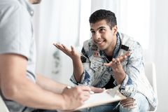 Smiling spanish teenager consulting youth problems with therapist royalty free stock photo