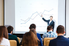 Smiling speaker standing and explaining graphs on business conference stock photography