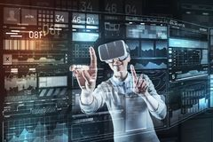 Smiling specialist choosing a program while wearing virtual reality glasses. Choosing program. Cheerful professional young programmer looking glad while wearing Stock Images