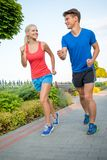 Smiling sport couple running in park Stock Photography