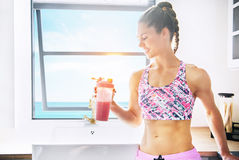 Smiling sportive person holding shaker with drink. Happy healthy young woman standing near window and holding shaker with drink. Horizontal indoors shot Royalty Free Stock Photos