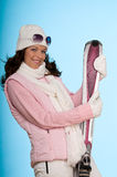 Smiling sportive woman holding pink skis Stock Image