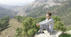 Smiling sportive woman on rock Stock Photography