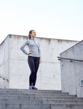 Smiling sportive woman on stairs at city Royalty Free Stock Image