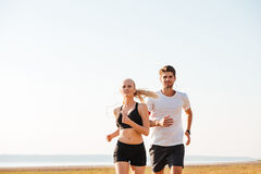 Smiling sports couple running outdoors Stock Images