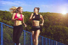 Smiling sports girls on a run in the park. Healthy lifestyle.
