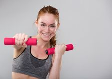 Smiling sports woman holding weights Stock Photography