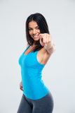 Smiling sports woman pointing finger at camera Stock Photography
