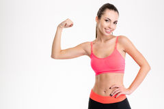 Smiling sports woman showing her bicep Royalty Free Stock Photography