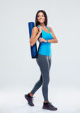 Smiling sports woman with yoga mat walking Royalty Free Stock Photos