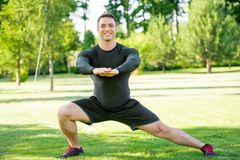 Smiling sportsman doing stretching exercise Stock Photos