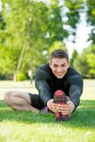 Smiling sportsman doing stretching on the grass Royalty Free Stock Photography