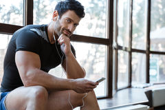 Smiling sportsman listening to music. Smiling sportsman wearing black t-shirt listening to music Stock Photography