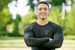 Smiling sportsman standing in the park Royalty Free Stock Photography