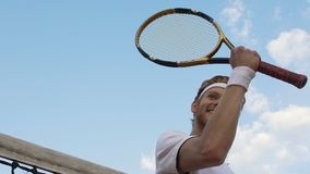 Smiling sportsman with tennis racket raising hand, victory gesture, slow motion