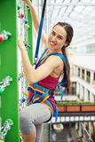 Smiling sportswoman is climbing on the wall with chains Royalty Free Stock Images