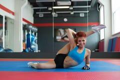 Smiling sportswoman doing stretching exercises Royalty Free Stock Photos